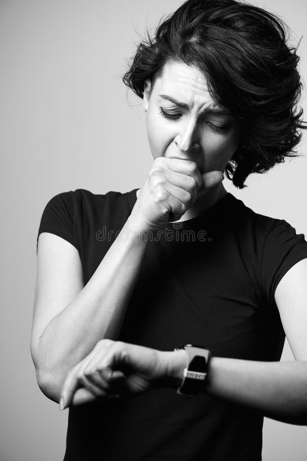 Γυναίκα που εξετάζει το ρολόι και το χασμουρητό στοκ φωτογραφίες