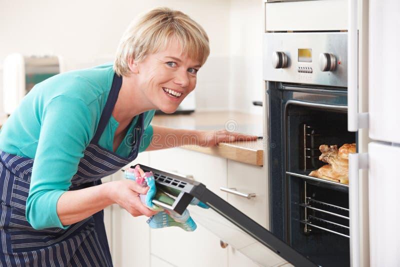 Γυναίκα που εξετάζει το ψήσιμο κοτόπουλου στο φούρνο στοκ φωτογραφία