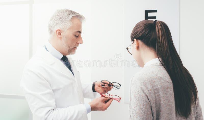 Γυναίκα που επιλέγει ένα ζευγάρι των γυαλιών στοκ φωτογραφία
