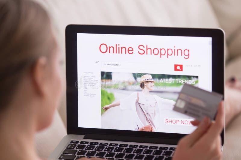 Γυναίκα που επιλέγει και που αγοράζει τα καθιερώνοντα τη μόδα ενδύματα on-line στοκ φωτογραφία