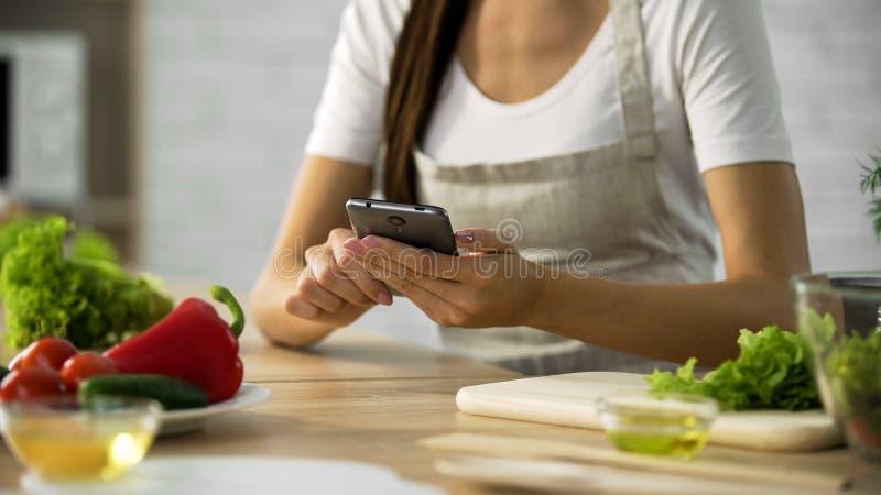 Γυναίκα που επιλέγει τη συνταγή σαλάτας στο smartphone στην κουζίνα, που μαγειρεύει την εφαρμογή στοκ εικόνα με δικαίωμα ελεύθερης χρήσης