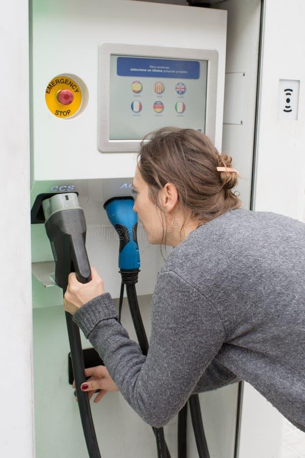Γυναίκα που επιλέγει το φορτιστή σε έναν σταθμό χρέωσης στοκ φωτογραφία με δικαίωμα ελεύθερης χρήσης