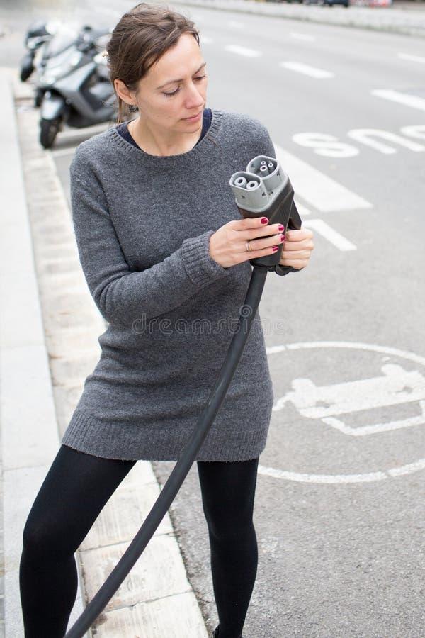 Γυναίκα που επιλέγει το φορτιστή σε έναν σταθμό χρέωσης στοκ φωτογραφίες