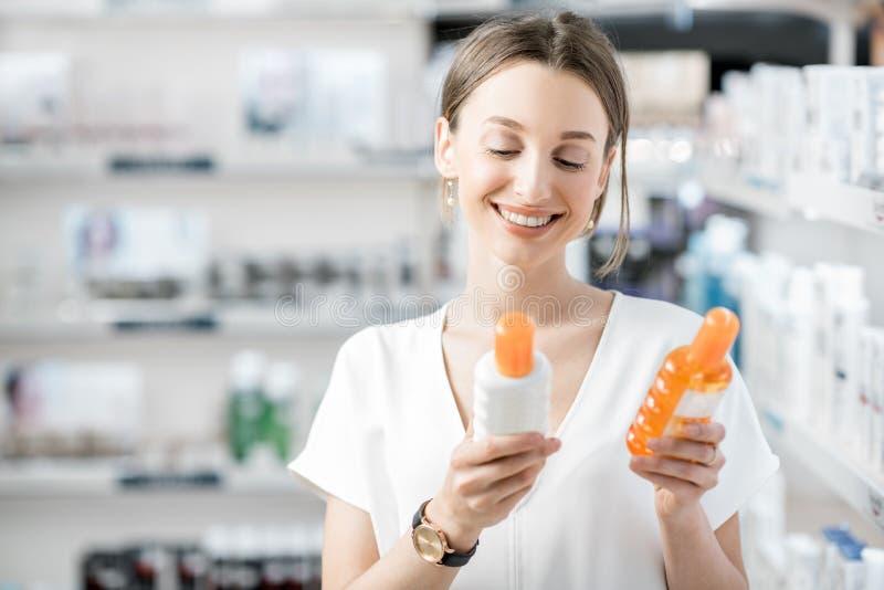 Γυναίκα που επιλέγει sunscreen το λοσιόν στο φαρμακείο στοκ εικόνα με δικαίωμα ελεύθερης χρήσης