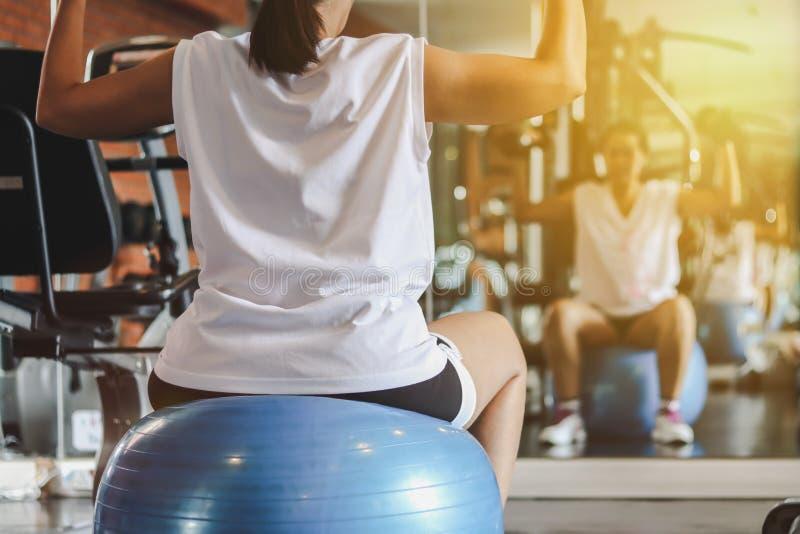 Γυναίκα που επιλύει με τους αλτήρες που κάθονται στη γυμναστική σφαίρα στοκ εικόνες