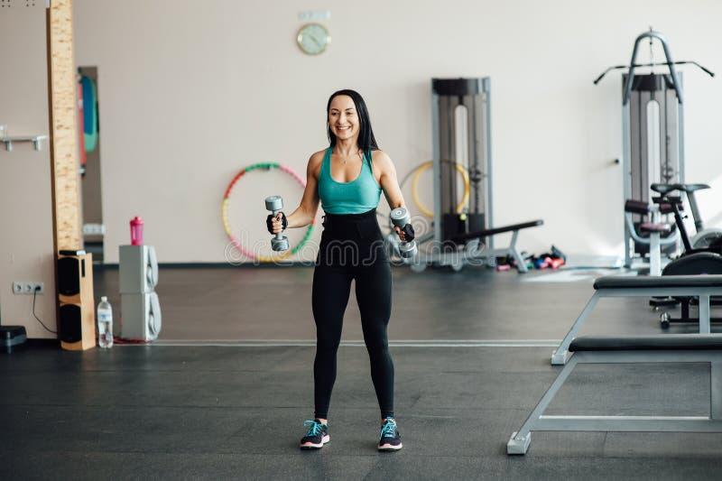 Γυναίκα που επιλύει με τους αλτήρες σε μια γυμναστική στοκ εικόνες με δικαίωμα ελεύθερης χρήσης