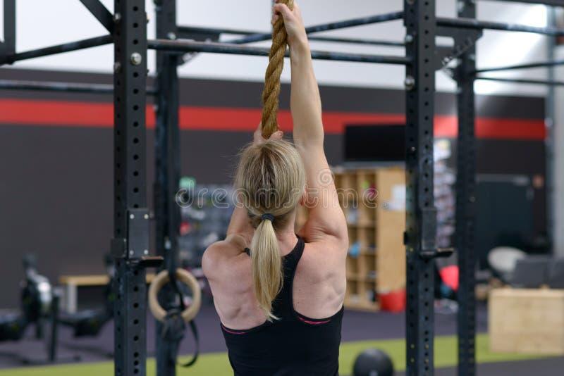 Γυναίκα που επιλύει σε ένα σχοινί σε μια γυμναστική στοκ εικόνες με δικαίωμα ελεύθερης χρήσης