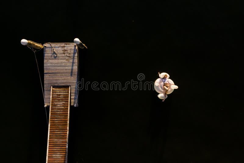 Γυναίκα που επιπλέει στον ωκεανό σε φουσκωτό κύκνο στοκ φωτογραφία με δικαίωμα ελεύθερης χρήσης