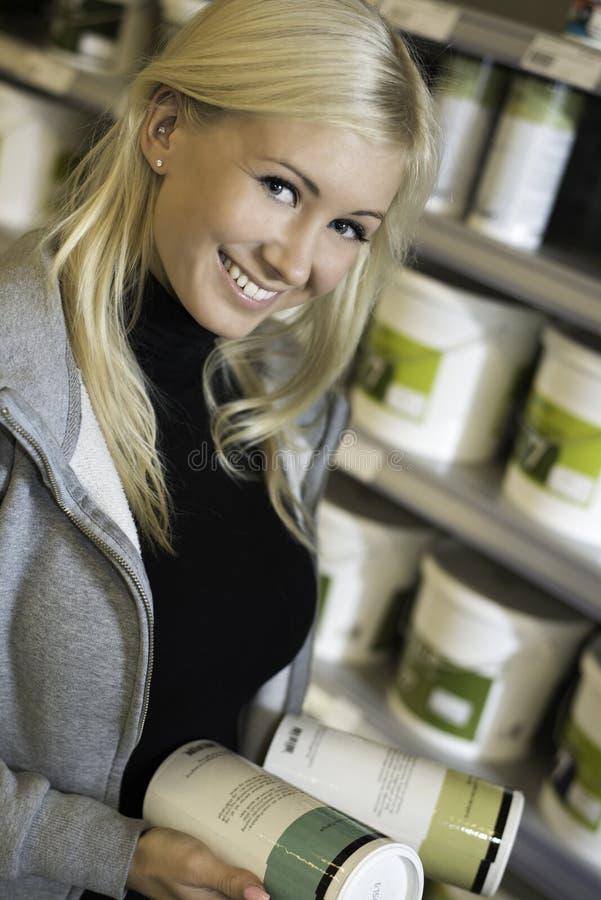 Γυναίκα που επιλέγει μεταξύ των προϊόντων στο κατάστημα υλικού στοκ φωτογραφίες