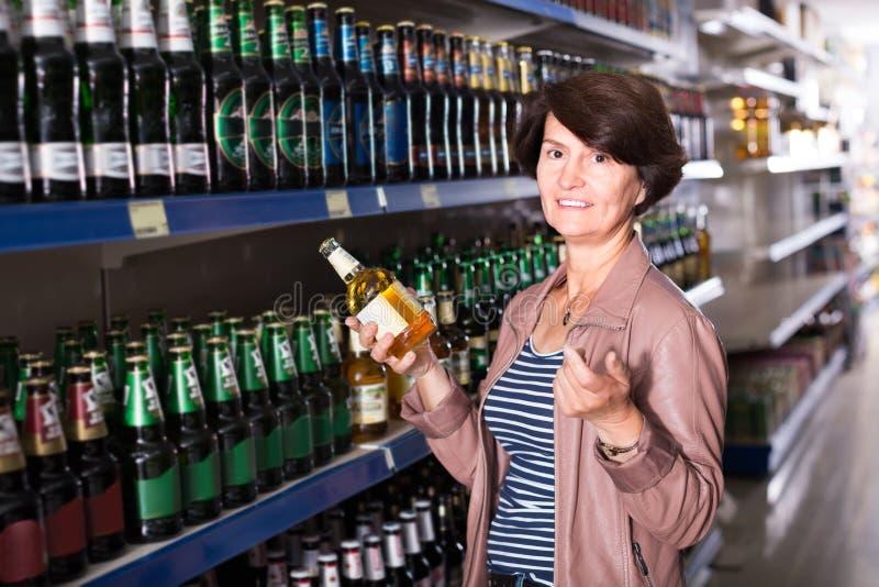 Γυναίκα που επιλέγει την μπύρα στο κατάστημα στοκ φωτογραφίες με δικαίωμα ελεύθερης χρήσης