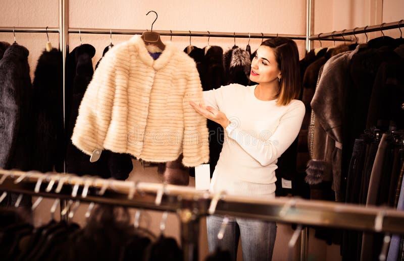Γυναίκα που επιλέγει το άσπρο σακάκι βιζόν στο κατάστημα υφασμάτων women's στοκ φωτογραφία με δικαίωμα ελεύθερης χρήσης
