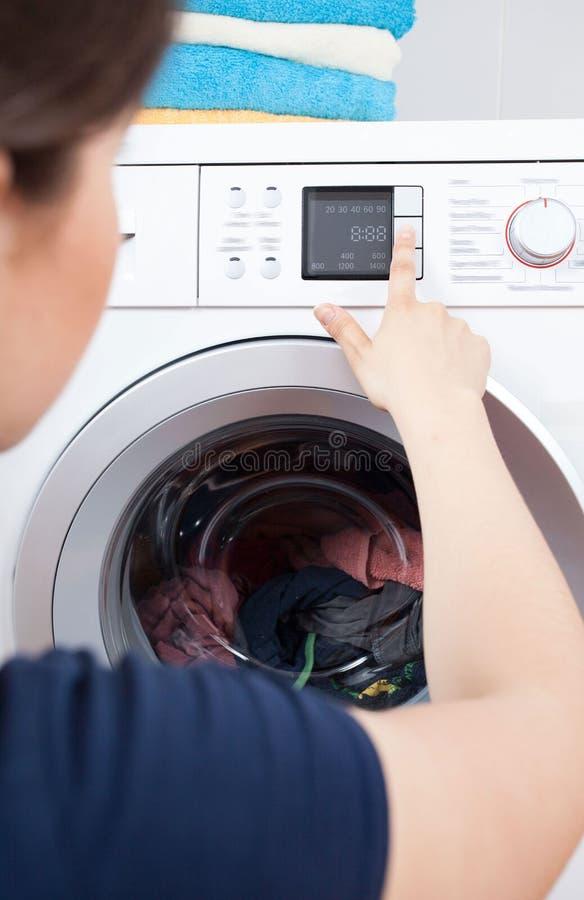 Γυναίκα που επιλέγει το πρόγραμμα πλύσης για ένα πλυντήριο στοκ φωτογραφία