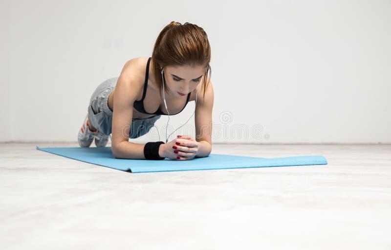 Γυναίκα που επιλύει στο χαλί γιόγκας στοκ εικόνες