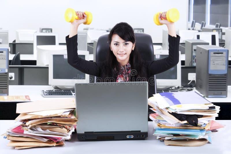 Γυναίκα που εργάζεται και workout στο γραφείο 2 στοκ εικόνες