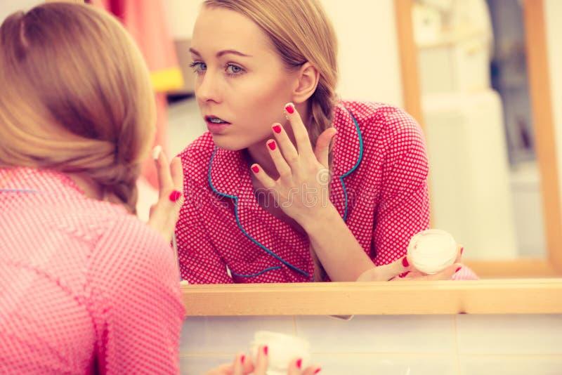 Γυναίκα που εφαρμόζει την ενυδατική κρέμα δερμάτων Skincare στοκ φωτογραφίες