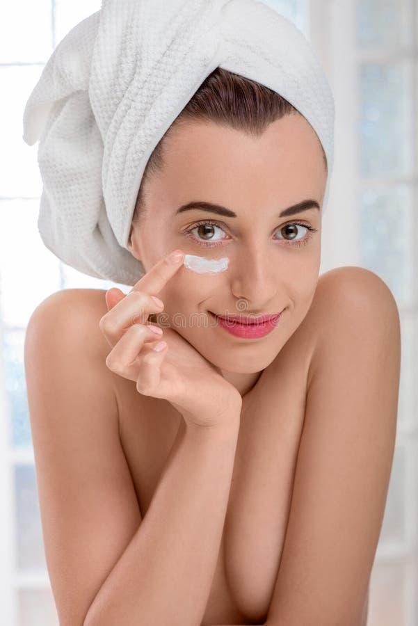 Γυναίκα που εφαρμόζει την καλλυντική κρέμα στο πρόσωπό της στοκ εικόνες με δικαίωμα ελεύθερης χρήσης