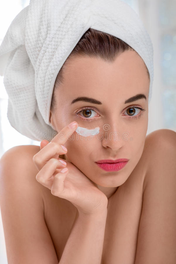 Γυναίκα που εφαρμόζει την καλλυντική κρέμα στο πρόσωπό της στοκ εικόνες