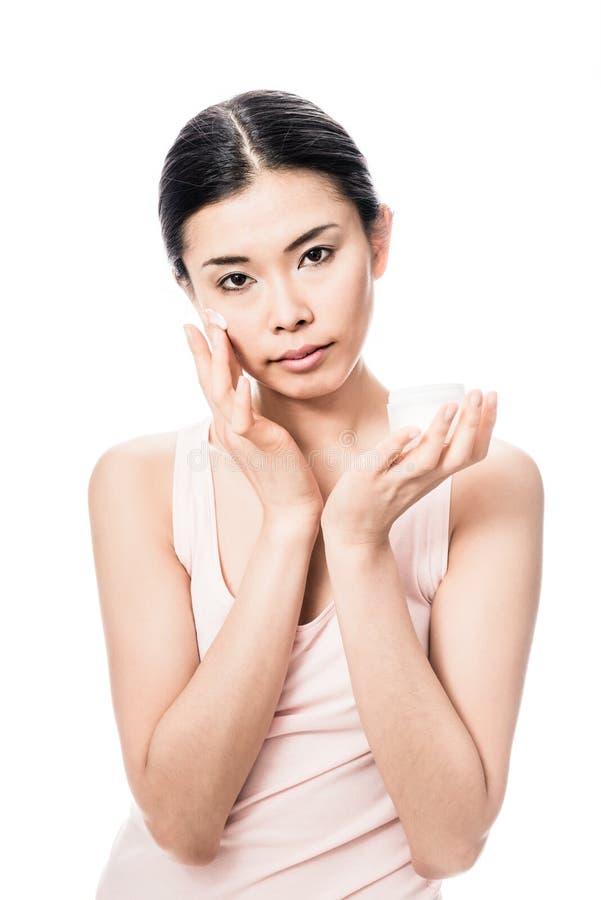Γυναίκα που εφαρμόζει την του προσώπου κρέμα moisturizer για το ευαίσθητο δέρμα στοκ εικόνες