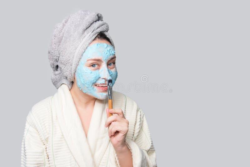 Γυναίκα που εφαρμόζει την του προσώπου μάσκα αργίλου στο σαλόνι SPA ή στο σπίτι, skincare θέμα Μάσκα προσώπου, επεξεργασία ομορφι στοκ φωτογραφία