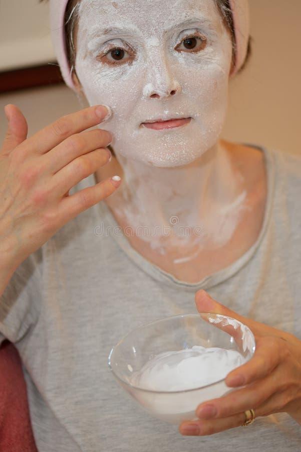 Γυναίκα που εφαρμόζει τη μάσκα σκονών μαργαριταριών στοκ εικόνες