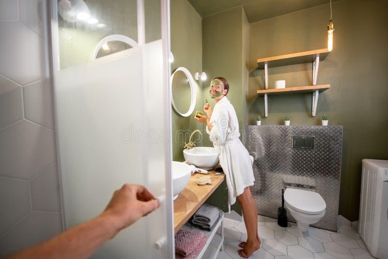 Γυναίκα που εφαρμόζει τη μάσκα στο πρόσωπό της στο λουτρό στοκ φωτογραφία με δικαίωμα ελεύθερης χρήσης