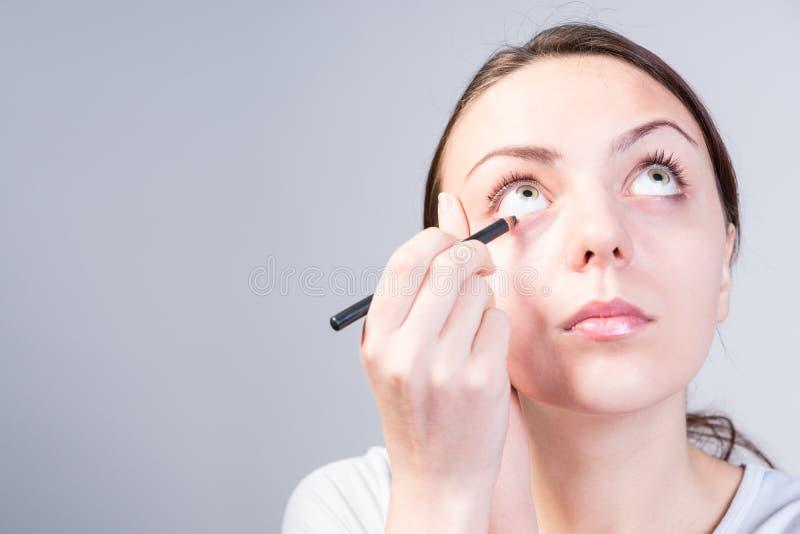 Γυναίκα που εφαρμόζει Eyeliner Makeup ανατρέχοντας στοκ εικόνες με δικαίωμα ελεύθερης χρήσης