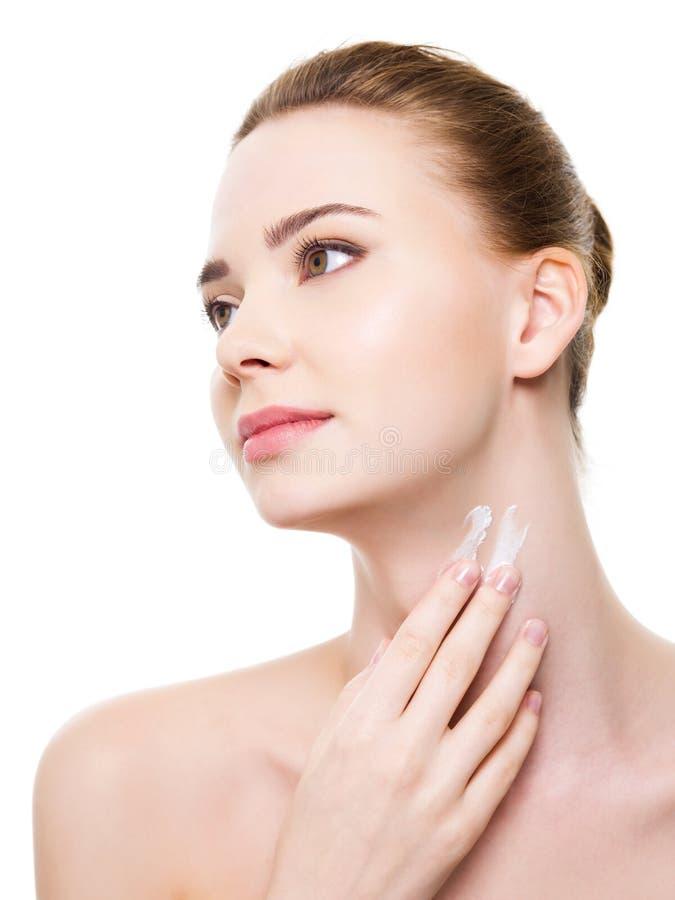 Γυναίκα που εφαρμόζει moisturizer το καλλυντικό στο λαιμό στοκ φωτογραφίες