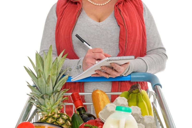Γυναίκα που ελέγχει τον κατάλογο αγορών τροφίμων της στοκ φωτογραφία