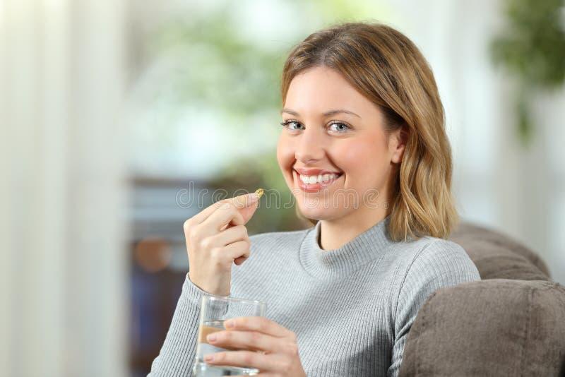 Γυναίκα που θέτει κρατώντας ένα χάπι βιταμινών έτοιμο να πάρει στοκ εικόνες