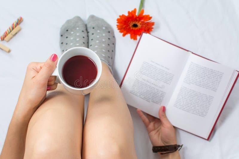 Γυναίκα που διαβάζει ένα βιβλίο και που έχει το φλυτζάνι του τσαγιού στοκ εικόνες