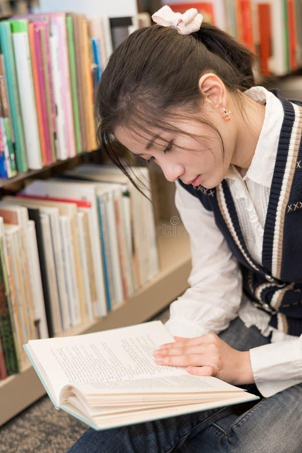 Γυναίκα που διαβάζει ένα βιβλίο κοντά στο ράφι στοκ εικόνα