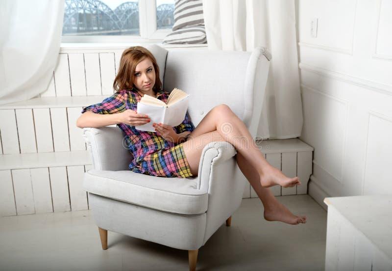 Γυναίκα που διαβάζει ένα βιβλίο στον καναπέ στοκ φωτογραφία με δικαίωμα ελεύθερης χρήσης
