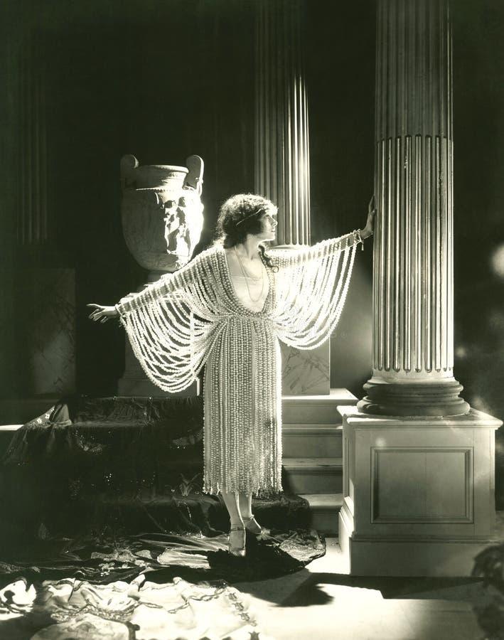 Γυναίκα που διαμορφώνει ένα φόρεμα φιαγμένο από μαργαριτάρια στοκ εικόνα
