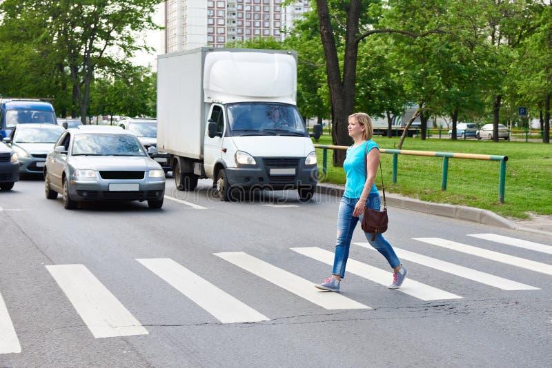 Γυναίκα που διασχίζει την οδό στο για τους πεζούς πέρασμα στοκ εικόνες