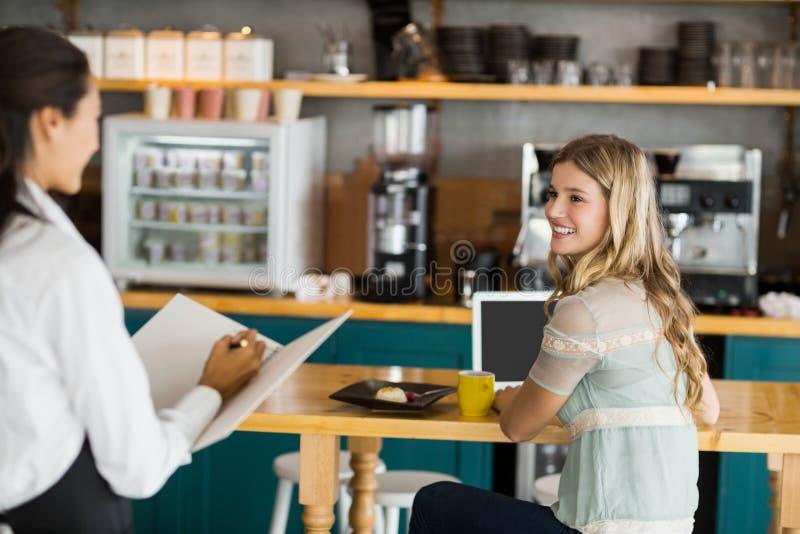 Γυναίκα που διατάζει τον καφέ από τη σερβιτόρα στοκ φωτογραφίες