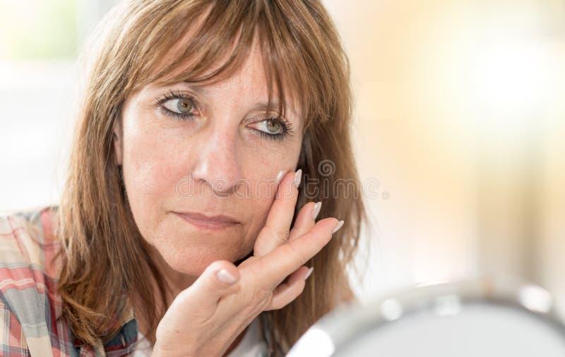 Γυναίκα που ισχύει moisturizer στο πρόσωπό της, ελαφριά επίδραση στοκ εικόνα