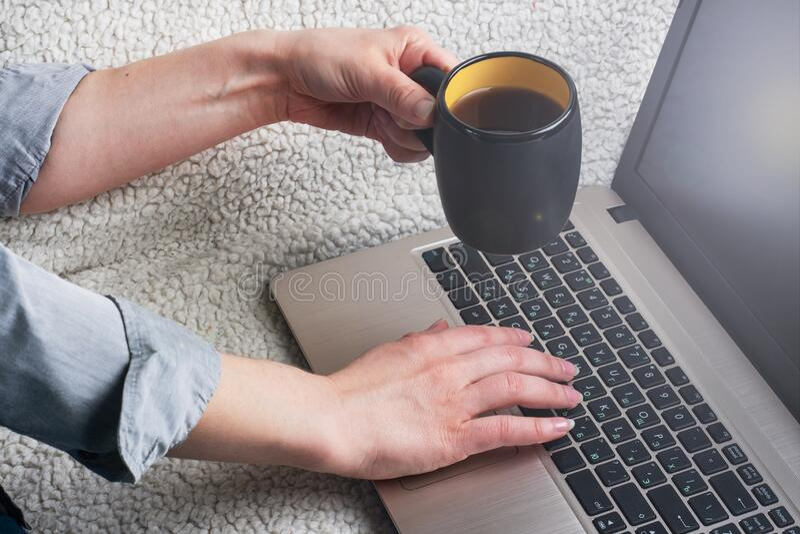 Γυναίκα που κάθεται σε έναν καναπέ και εργάζεται σε χέρια υπολογιστή Κλείσιμο στοκ εικόνα με δικαίωμα ελεύθερης χρήσης