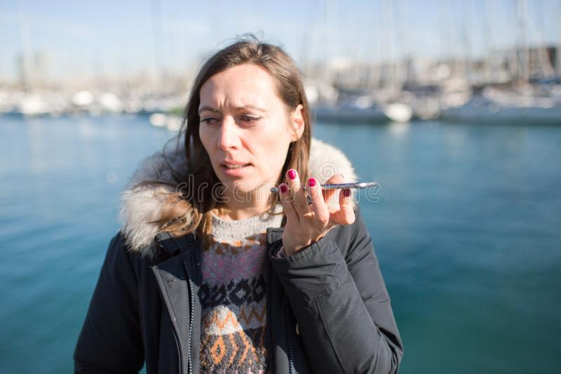 Γυναίκα που κάνει ένα μασάζ φωνής στο τηλέφωνο στοκ φωτογραφία με δικαίωμα ελεύθερης χρήσης
