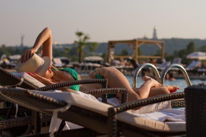Γυναίκα που κάνει ηλιοθεραπεία σε έναν αργόσχολο στοκ φωτογραφία