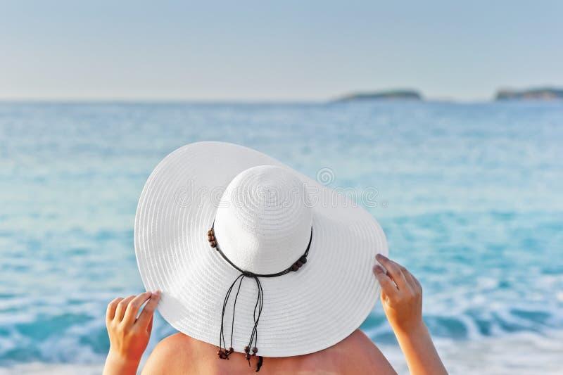 Γυναίκα που κάνει ηλιοθεραπεία σε μια καρέκλα γεφυρών στην παραλία και που κρατά το καπέλο χεριών στοκ εικόνες
