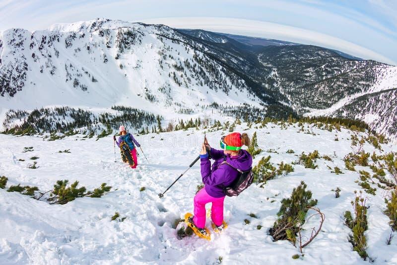 Γυναίκα που κάνει πεζοπορία στα χιονισμένα βουνά με ένα τηλέφωνο και παπούτσια χιονιού και σακίδιο στοκ φωτογραφία με δικαίωμα ελεύθερης χρήσης