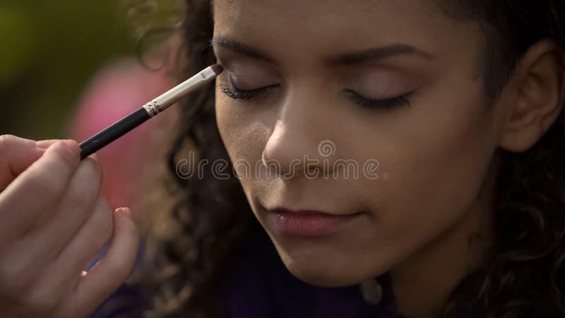 Γυναίκα που κάνει τα καπνώδη μάτια makeup, προετοιμάζοντας την όμορφη ηθοποιό για το πυροβολισμό ταινιών στοκ εικόνες