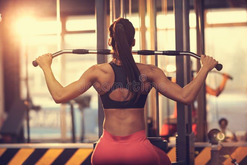 Γυναίκα που κάνει την άσκηση για το στήθος και την πίσω, πίσω άποψη στοκ φωτογραφία