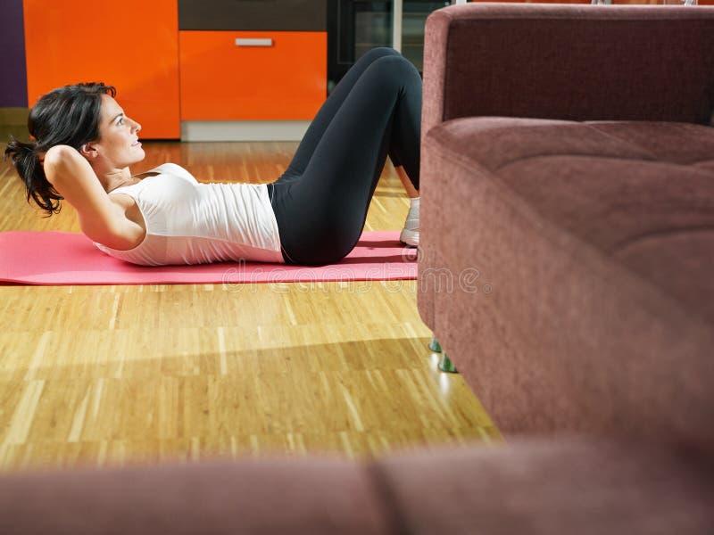 Γυναίκα που κάνει την άσκηση ABS στο σπίτι στοκ εικόνες με δικαίωμα ελεύθερης χρήσης