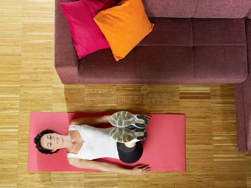 Γυναίκα που κάνει την άσκηση ABS στο σπίτι στοκ εικόνες