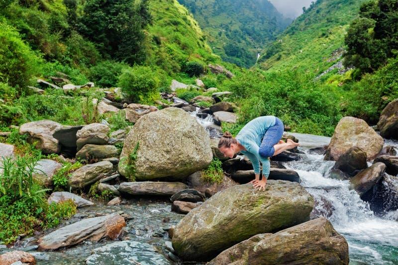 Γυναίκα που κάνει την ισορροπία βραχιόνων asana Kakasana υπαίθρια στοκ φωτογραφία