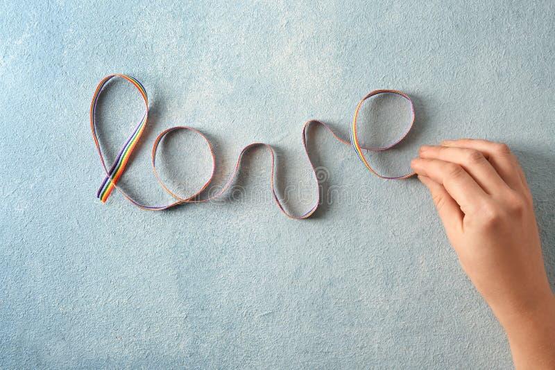 Γυναίκα που κάνει την κορδέλλα ουράνιων τόξων λέξης Με αγάπη από LGBT στο υπόβαθρο χρώματος στοκ εικόνες με δικαίωμα ελεύθερης χρήσης