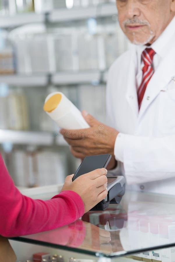 Γυναίκα που κάνει την πληρωμή NFC ενώ μπουκάλι σαμπουάν εκμετάλλευσης φαρμακοποιών στοκ φωτογραφία