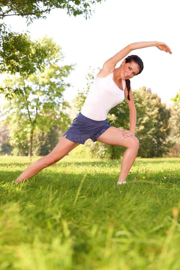 Γυναίκα που κάνει την τεντώνοντας άσκηση στην πράσινη χλόη στοκ εικόνα με δικαίωμα ελεύθερης χρήσης