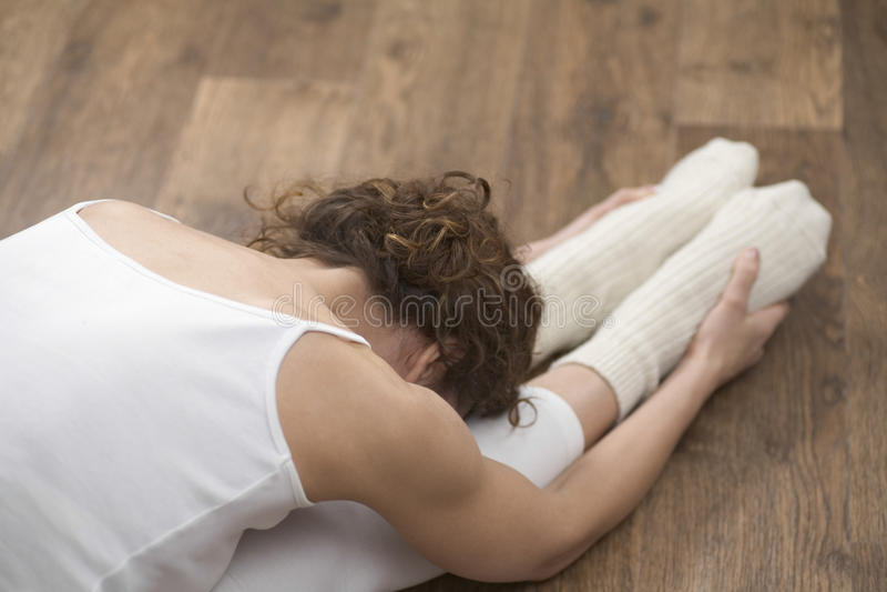Γυναίκα που κάνει την τεντώνοντας άσκηση στο πάτωμα σκληρού ξύλου στοκ εικόνα